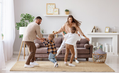 happy family mother father and children dancing at home .