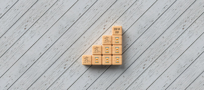 cubes forming a stair with people symbols and message STEP BY STEP wooden background