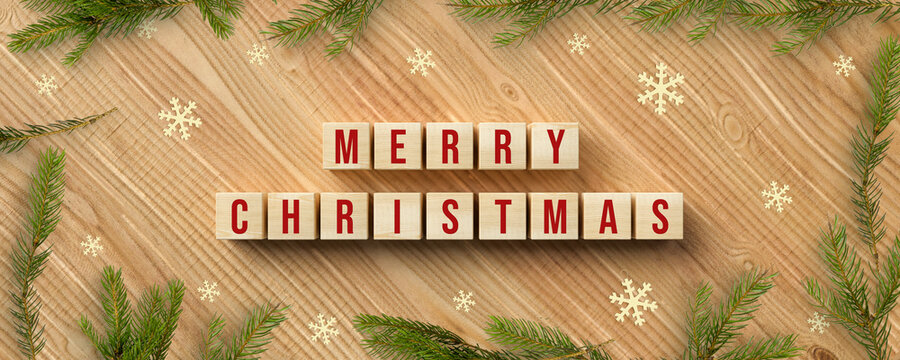 cubes with message MERRY CHRISTMAS and christmas decoration on wooden background
