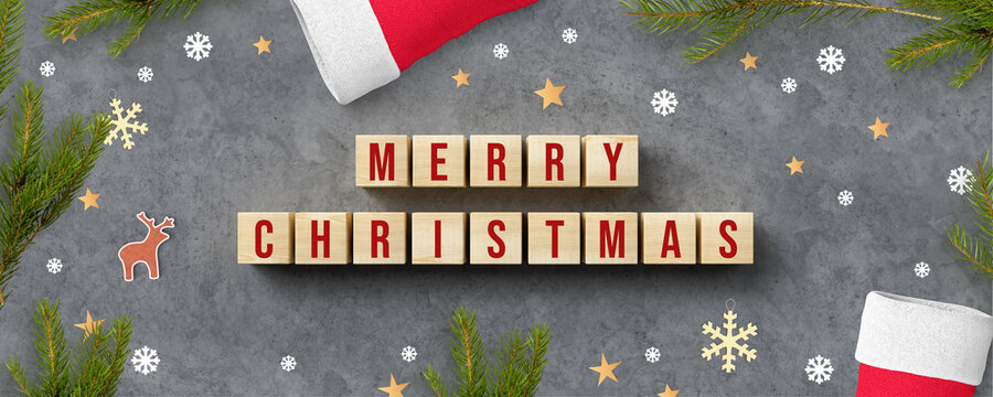 cubes with message MERRY CHRISTMAS and christmas decoration on concrete background