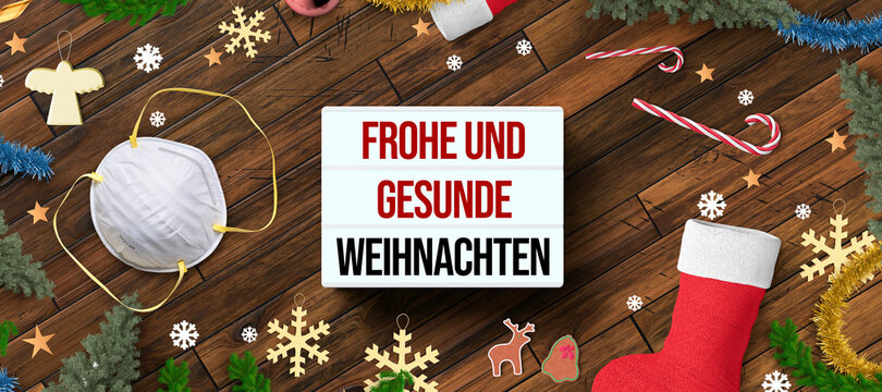 christmas decoration on wooden background and lightbox with German message for HAPPY AND HEALTHY CHRISTMAS