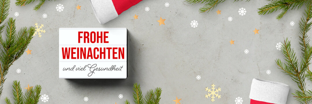 lightbox with German message for MERRY CHRISTMAS AND GOOD HEALTH and christmas decoration on concrete background