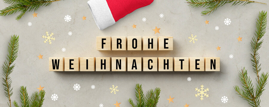 cubes with German message for MERRY CHRISTMAS and christmas decoration on concrete background