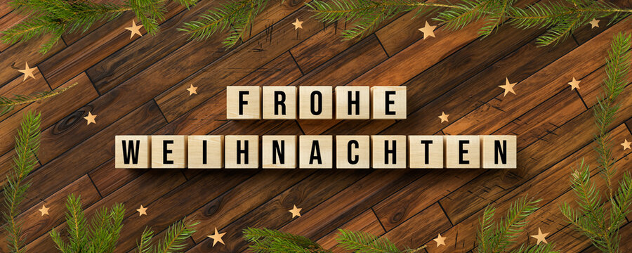 cubes with German message for MERRY CHRISTMAS and christmas decoration on wooden background