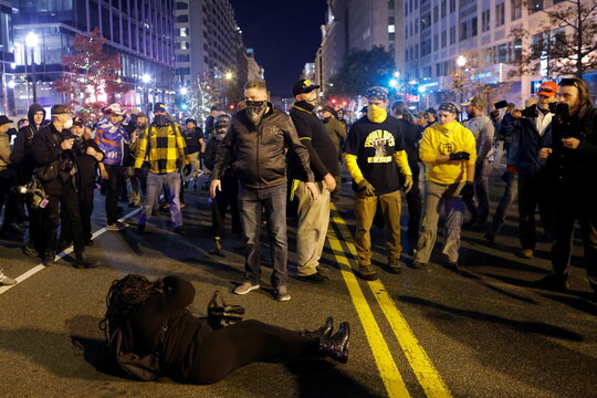 A woman lies on the ground surrounded by members of far-right militia Proud Boys during a scuffle following a protest against election results, in Washington, U.S.
