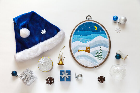 Handmade gifts for Christmas. Long stitch embroidery on a winter theme. Gift boxes, Christmas toys and a blue Santa hat on a white background. DIY concept. Flat lay, close-up, top view