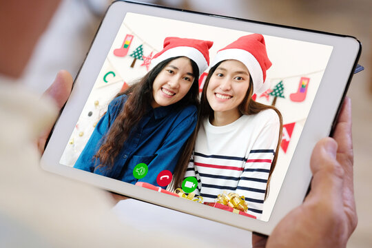 Two asian girl video call to family for greeting in Christmas celebration, Senior man hand holding digital tablet while talking with daughter in Christimas season, new normal, online party celebrating