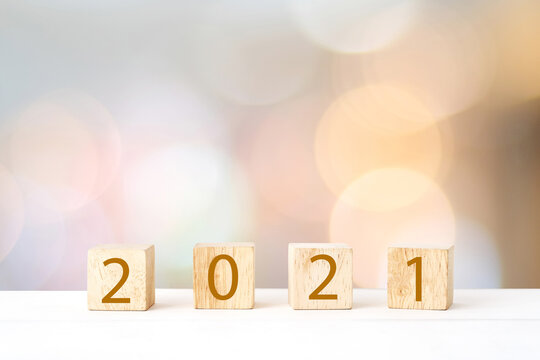 Happy New Year 2021 on wood cube block and blur abstract bokeh light background with cop space for text, Happy new year 2021 greeting card, banner