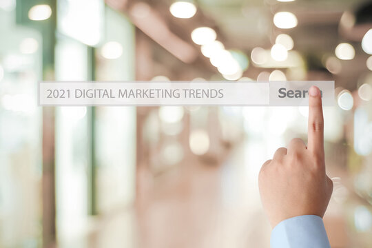 Man hand touching 2021 digital marketing trend, business strategy, on search bar over blur office background, success in business concept