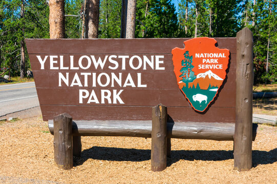 Entrance sign to to Yellowstone National Park with National Park Service arrowhead insignia - Yellowstone National Park, Wyoming, USA - 2020