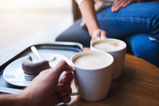 Closeup image of two people clink white coffee mugs on wooden table in cafe