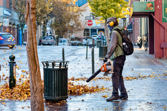 man blowing leaves on a street