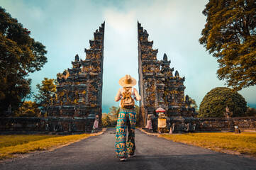 Woman with backpack walking at big entrance gate in Bali, Indonesia. Wall mural