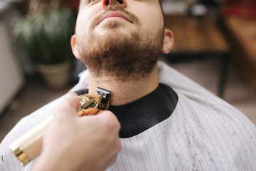 Professional hairdresser uses a hair clipper for fringing beard for a handsome man in barbershop