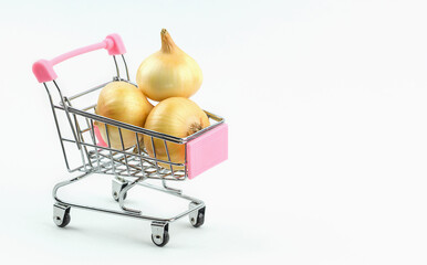 Shopping cart with fresh onions on a white background.