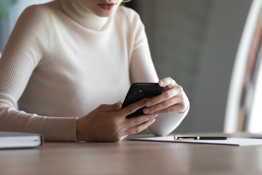 Close up businesswoman using smartphone, looking at screen, sitting at desk in modern office, focused female employee worker holding phone in hands, browsing apps, checking email, chatting online