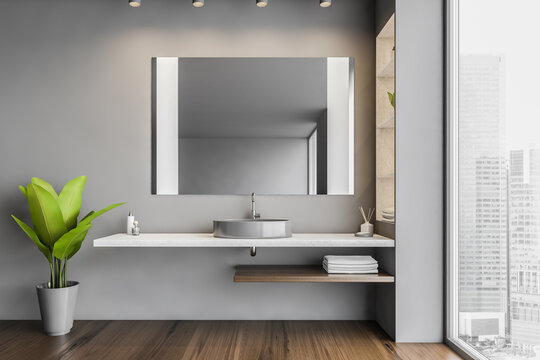 Dark open space bathroom with sink and mirror and a big window