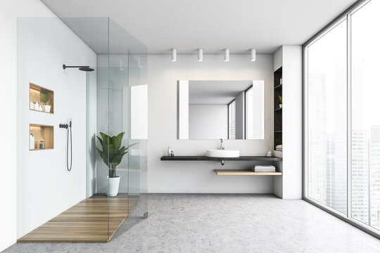 White bathroom with shower cabin and sink with mirror near big window