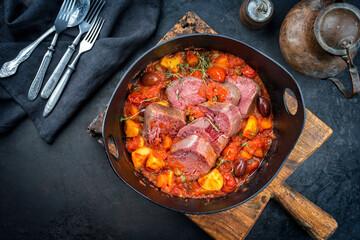 Modern Style traditionelle peruanische estofado de lengua gekochte Rinderzunge mit Gemüse und Oliven als Eintopf in einem Design Guss Topf