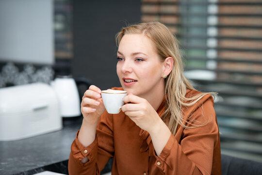 Kaffeepause im Job - junge Angestellte genießt eine Tasse Milchkaffee in der Teeküche, Symbolfoto.