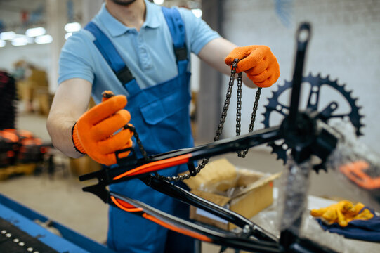 Bicycle factory, worker holds bike chain