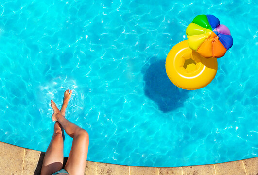 Woman's legs on the border and inflatable yellow sun umbrella buoy swim in the swimming pool view from above