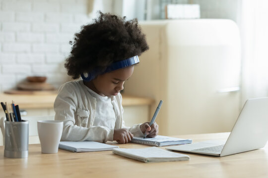 Serious African American little girl wearing headphones writing notes, studying online, pretty child schoolgirl doing homework, sitting at table with laptop at home, homeschooling concept