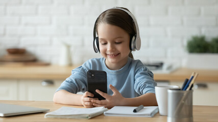 Smiling little girl wearing headphones using phone close up, distracted from studying, sitting at...