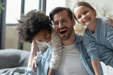Overjoyed father with two daughters having fun, playing funny game close up, excited dad wearing...