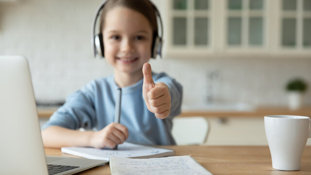 Close up happy little girl wearing headphones showing high five, studying online, sitting at table with laptop and notebooks at home, recommending remote internet education and homeschooling
