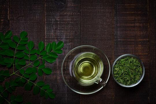 Moringa Tea on wooden background. Moringa oleifera tropical herb healthy lifestyle concept.