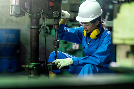 asian female worker wearing safty uniform and goggle technician or turner girl use the screw machine to drill the metal product in the factory workshop workplace.