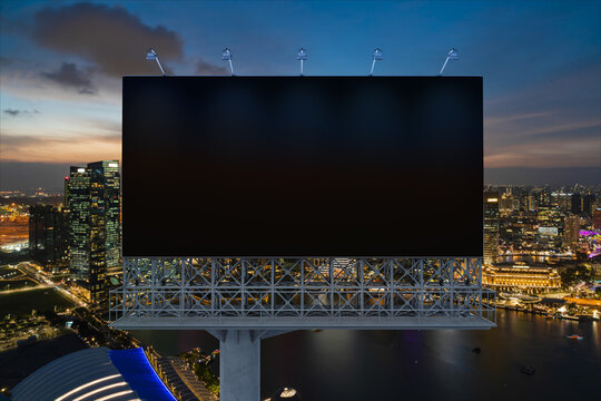 Blank black road billboard with Singapore cityscape background at night time. Street advertising poster, mock up, 3D rendering. Front view. The concept of marketing communication to sell idea.