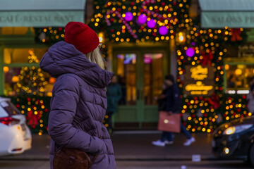 Christmas lights urban street view with woman in coat back to camera enjoy by festive decorations Fotomurales