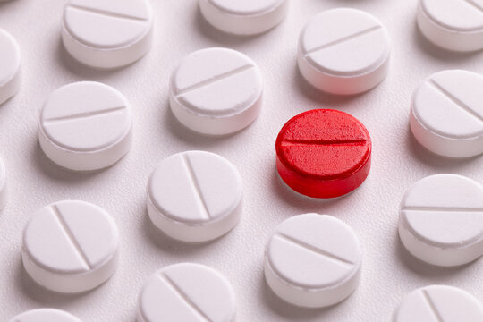 White round medicine tablets. Round medicine pills background. White and red pills.