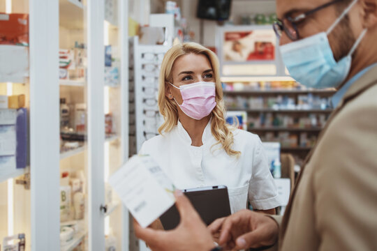 Young business man choosing and buying drugs in a drugstore while talking with female pharmacist. She helping him with expert advice. They are wearing protective face masks against virus infection.