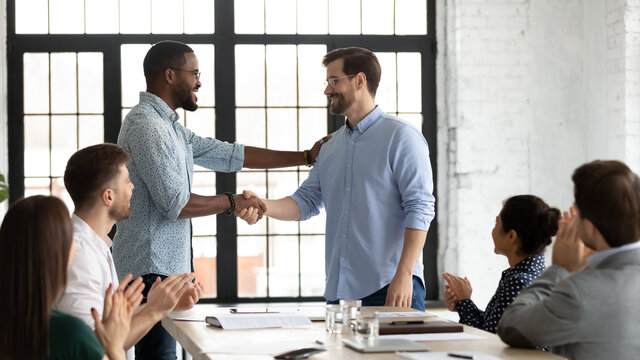 Perfect job. Friendly african american boss or team leader shaking hand of happy excited caucasian employee manager worker on staff meeting at boardroom demonstrating respect greeting with promotion