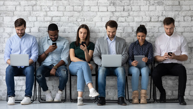 Modern way to communicate. Row of diverse young people sitting close to wall holding different gadgets cellphones laptops pads surfing internet chatting browsing social networks work or study online
