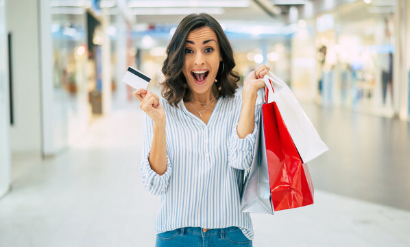 Excited gorgeous smiling young woman is posing with a credit card and shopping bags in the mall