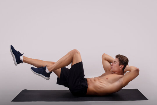 Strong young guy with bare torso doing abs exercises on yoga mat against light studio background, side view