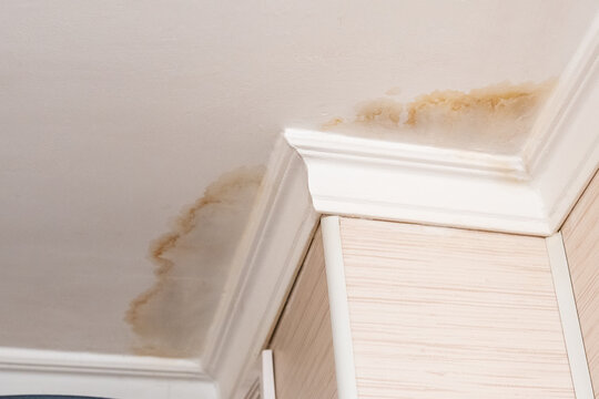 Neighbors have a water leak, water-damaged ceiling, close-up of a stain on the ceiling