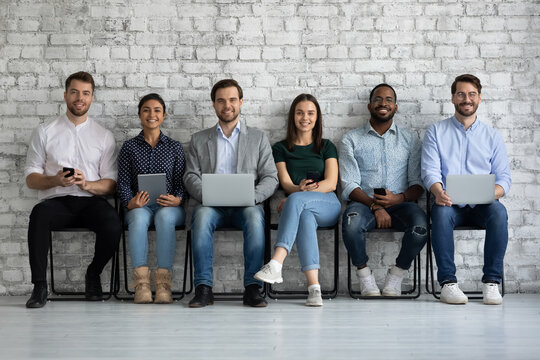 Portrait of young happy people of different gender and ethnicity job applicants business team group of clients posing on chairs in queue with diverse modern gadgets in hands smiling looking at camera