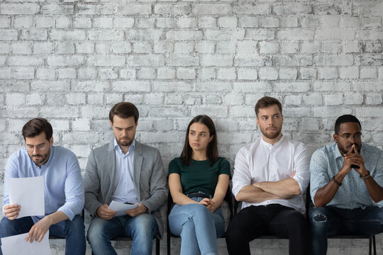 Expecting employer decision. Worried nervous multiethnic young people candidates on vacant place sitting in row at office hall waiting for private conversation with hr or announcing competition result