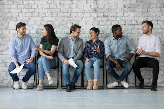 Sharing impressions. Couples of diverse multinational businesspeople job seekers students sitting on chairs in office university hallway talking exchanging opinions discussing interview exam results