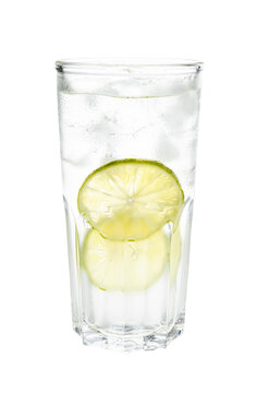 side view of gin and tonic cocktail in highball glass with two slices of lime and ice isolated on white background