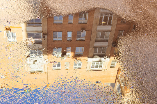 rain puddle with reflection of high-rise apartment house on surface of asphalt road in city on sunny autumn day