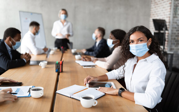 Businesswoman In Face Mask Sitting Attending Corporate Meeting In Office