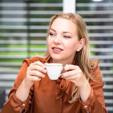 Kaffeepause - attraktive Sekretärin genießt eine Tasse Milchkaffee im Büro. Symbolfoto.