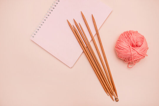 Notepad, colored balls of yarn and knitting needles isolated on a pink background. needlework, creativity. what to do on self-isolation. learn to knit. space for text