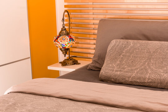 Oriental lamp on wooden nightstand next to bed with wooden headboard